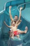 Bras d'And Son With de père tendus sur la glissière d'eau Image stock