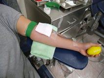 Bras de doner de sang pendant le don du sang images stock