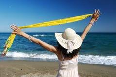 Bras de femme tendus par la mer Photographie stock