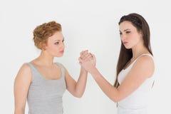 Bras de fer femelle sérieux de deux jeune amis Image libre de droits
