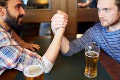 Bras de fer masculin heureux d'amis à la barre ou au bar Image libre de droits
