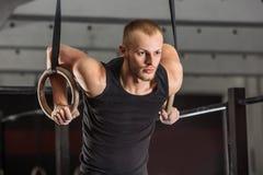 Bras de formation d'homme de forme physique avec des anneaux de gymnastique photos stock