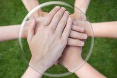 Bras de mains unissant dans la sphère en verre Images stock