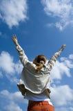 Bras de propagation de femme au ciel Photo stock