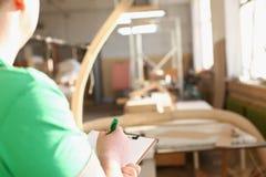 Bras de travailleur faisant des notes sur le presse-papiers avec le stylo vert Photos stock