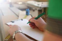 Bras de travailleur faisant des notes sur le presse-papiers avec le stylo vert photographie stock libre de droits