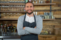 Bras debout de barman masculin croisés dans le café Photo stock