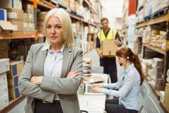 Bras debout de directeur sérieux d'entrepôt croisés photographie stock libre de droits