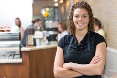 Bras debout de propriétaire heureux croisés en café images stock