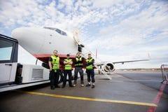 Bras debout sûrs de personnel de piste croisés contre l'avion photos libres de droits