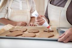 Bras femelles habiles décorant les biscuits qui a réussi tout seul Photo libre de droits