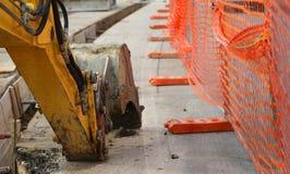 Bras mécanique de l'excavatrice creusant sur la route Photo libre de droits