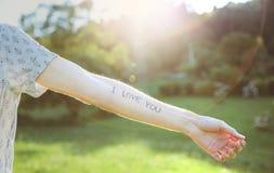 Bras masculin avec le texte - amour d'I vous écrit dans la peau Photographie stock libre de droits