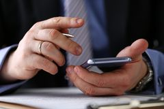 Bras masculin dans le stylo de téléphone et d'argent de prise de costume au plan rapproché de lieu de travail images stock