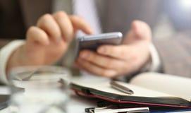 Bras masculin dans le stylo de t?l?phone et d'argent de prise de costume photo libre de droits
