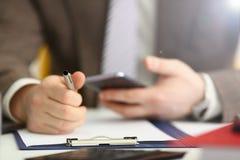Bras masculin dans le stylo de t?l?phone et d'argent de prise de costume image stock