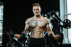 Bras modèles beaux de formation de jeune homme dans le gymnase Photo stock