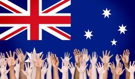 Bras multi-ethniques augmentés et fond australien de drapeau Photos stock