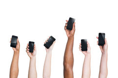 Bras multi-ethniques soulevant des Smartphones et une position  Photos stock
