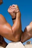 Bras musculeux sous le ciel bleu Images libres de droits