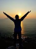 Bras ouverts de femme reconnaissante au lever de soleil Photographie stock