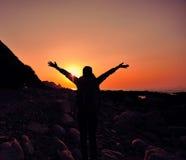 Bras ouverts de femme reconnaissante au lever de soleil Images stock