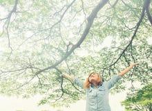 Bras ouverts de jeune femme se tenant dans la verdure fraîche de ressort avec elle Image libre de droits