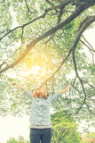 Bras ouverts de jeune femme se tenant dans la verdure fraîche de ressort avec elle Images libres de droits