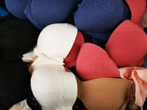 Bras various colors and sizes. Piled in a basket and ready for sale stock images