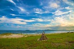 Brasa av trä på stranden nära havet runt om de dekorerade stenarna Royaltyfri Fotografi