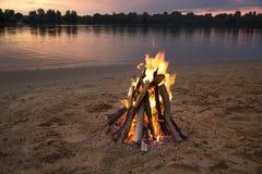 Brasa på banken av floden på solnedgången royaltyfri bild