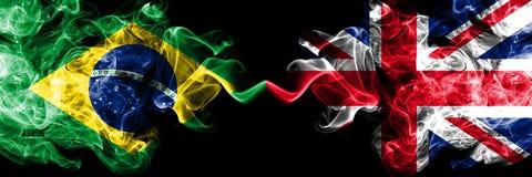Brasil contra Reino Unido, bandeiras britânicas do fumo colocadas de lado a lado Bandeiras de seda coloridas grossas do fumo do  ilustração stock
