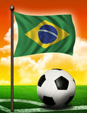 Brasil flag and ball. On soccer field Royalty Free Stock Photo