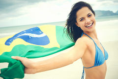 Brasil flag woman fan. Latino woman with Brasil flag laughing and smiling in support of Brazilian soccer fan royalty free stock photography