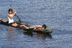 Brasil: Uma moça e um menino paddeling no Rio Amazonas perto de Paritins fotos de stock royalty free