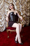 Brasilian Girl. Beautiful girl with leather corset seated in armchair Royalty Free Stock Photography