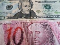 brasilianische Banknote von 10 Reais und Dollarschein des Amerikaners zwanzig, Hintergrund und Beschaffenheit Lizenzfreie Stockfotografie
