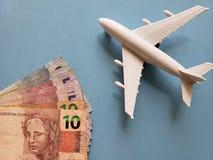 brasilianische Banknoten, weißes Plastikflugzeug und blauer Hintergrund lizenzfreie stockfotos