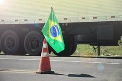 Brasilianische Flagge auf einem roten Verkehrskegel einer Landstraße mit verwischt Lizenzfreie Stockbilder