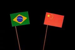 Brasilianische Flagge mit der chinesischen Flagge lokalisiert auf Schwarzem Lizenzfreies Stockfoto