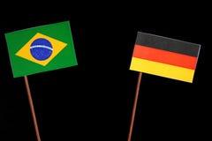 Brasilianische Flagge mit der deutschen Flagge lokalisiert auf Schwarzem Stockbild