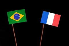 Brasilianische Flagge mit der französischen Flagge lokalisiert auf Schwarzem Stockbild