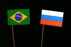 Brasilianische Flagge mit der russischen Flagge lokalisiert auf Schwarzem Stockfotografie