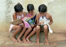 Brasilianische Mädchenlesebücher auf Straßenseite Lizenzfreie Stockfotografie