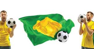 Brasilianischer Fan, der auf weißem Hintergrund feiert Der junge Mann in der Fußballfußballuniform mit dem Ball, der am Weiß steh Stockfotos