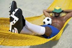 Brasilianischer Fußball-Spieler entspannt sich mit Fußball in der Strand-Hängematte lizenzfreies stockfoto