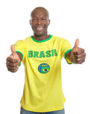 Brasilianischer Fußballfan, der beide Daumen zeigt Lizenzfreie Stockfotografie