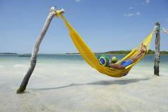 Brasilianischer Mann, der in der Strand-Hängematte mit trinkender Kokosnuss sich entspannt Lizenzfreie Stockfotografie