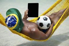 Brasilianischer Mann, der mit Tablet-und Fußball-Strand-Hängematte sich entspannt stockfotografie