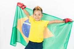 Brasilianischer Patriotjunge, der Brasilien-Flagge hält Verpackenmeisterschaft Stockbild